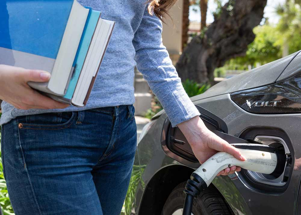 person charging electric car using charging station with EV Connect software